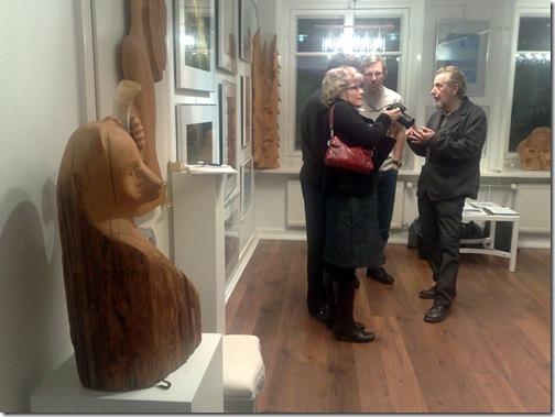 Puutaiteilija Tere Tolvanen keskustelee näyttelyvieraiden kanssa. Taustalla myös valokuvaaja Harri Likki.